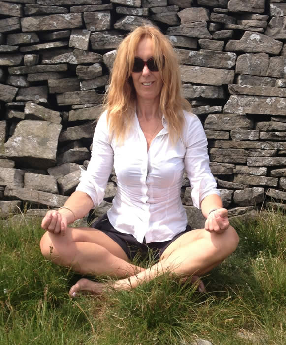 Anne Harrison practicing a seated yoga position outdoors